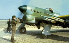 Hawker Typhoon, 1945 - Note the black spinner, the 2nd TAF [tactical airforce] painted their spinners black in 1945, they had been sky previously.  Note pilot in front in khaki battledress as well, I think for ease of concealment if shot down, and the 'erk' in the background holding a fire extinguisher, the Sabre engine engine used the Coffman starter system, which if didn't start up the engine first time it caused it burst into flames as it was primed full of petrol!