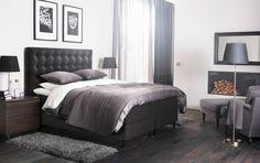 Dormitorio grande con una cama extragrande de color gris oscuro con cabecero tapizado y ropa de cama gris y blanca.