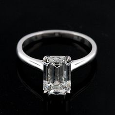 """This elegant 14k white gold solitaire engagement ring is pictured with one 2Ct emerald cut diamond set in delicate """"claw"""" prongs. The shank is rounded and high polish."""