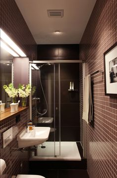 Narrow bathroom solution.  The glass shower door keeps the are feeling open.  The inset of the shelving and mirror stretches the space a bit more,