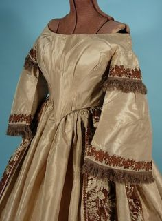 "Evening gown, circa 1860, shot taffetas and brocade, shown here with pagoda sleeves attached. Again, sleeves are edged in silk floss fringe, deep ""v"" at front of bodice, cartridge pleats, padded bosom, offered by Antique Dress"