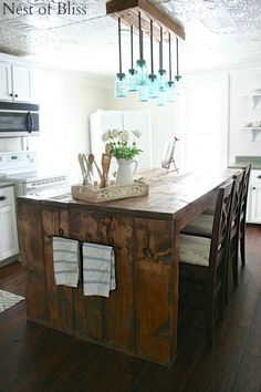 Farmhouse kitchen with fun jar chandelier and gorgeous rustic island