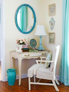 BHG:  A distressed vanity serves as a writing desk in a corner of a living room. The blue mirror above adds a punch of color to the cream walls. Reusing an old vase as a wastebasket maintains the vintage vibe of the room.