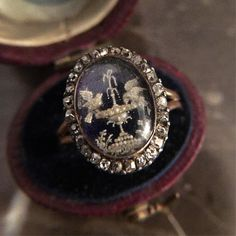 This super rare Georgian ring called to me today, and I answered. With diamond surround, the rock crystal covers a scene made from tiny seed pearls of two doves drinking from a fountain In Christian art, the seven gifts of the Holy Spirit are often seen as doves, perching on a tree or drinking the waters of Eternal life. Thus, we see them in art and jewelry -a pair of doves -one drinking, the other happily standing by -on the rim of a chalice-shaped vessel or fountain filled with water…