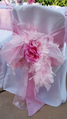 Dress up a plain chair cover with ribbons, tissue flowers and feathers. By using the one color, pink in this example, gives it an elegant flair!