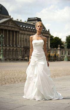 Prachtige strapless trouwjurk in off white tafta met parel afwerking op de top en een bloemaccent op de rok.