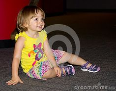 Two year old girl sitting happily on the floor while taking a break from activities.
