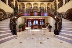 The home's grand, two-story foyer features a majestic double staircase with intricately detailed wrought iron railings. Luxurious marble tiles blanket the floor, completing the lavish look. Double Staircase, Grand Staircase, Staircase Design, Spiral Staircases, Wrought Iron Stairs, Iron Railings, Grand Foyer, Grand Entrance, Dream Mansion