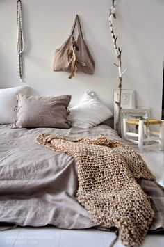 Bed on the floor with Earth tones and textiles