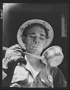Tennessee Valley Authority. Watts Bar Dam hydroelectric plant. A boilermaker working on the erection of a condenser at TVA's Watts Bar steam plant takes time out for a drink of water.  Photographer: Alfred T. Palmer June 1942
