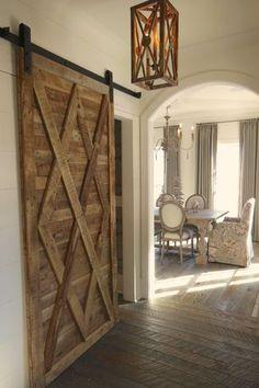 Country Hallway with Upholstered dining chair, Arch doorway, Barn door, Ash wood floor, Crown molding, Chandelier