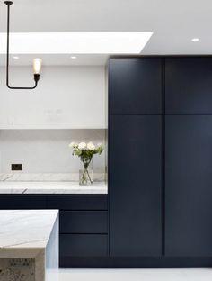 deco bleu canard, cuisine bleu, plafond blanc, luminaire en métal noir et ampoule, plan de travail en blanc, îlot avec plan en marbre blanc aux nervures noires, sol blanc