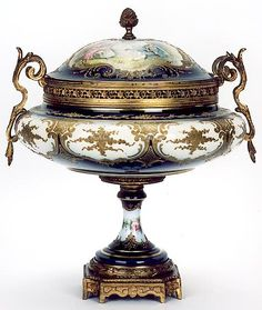 """FRENCH """"SEVRES"""" PORCELAIN COVERED DESSERT TUREEN CENTER PIECE. The cobalt blue and ivory/white field hand painted with panel of lovers in a bower, raised gold enamels highlight the designs. Ormolu curved handles, finial and base"""