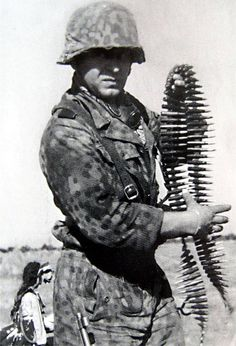 A Waffen-SS Grenadier in full M44 DOT camouflage uniform grabs a belt of linked 7.92 mm ammunition for the MG42 machine gun.