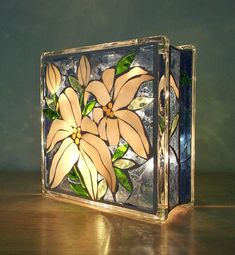 If you love flowers this one is for you! A brilliant stained glass light to enjoy in two different patterns. Lilies and roses, done on both sides of a glass block in shades of blues, very pale yellow, iridescent white, and a variety of greens. Photos were taken in with no sun, and #StainedGlassLight