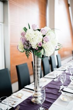 Tall Vase with White & Purple Flowers  Photography: Sterling Imageworks Read More: http://www.insideweddings.com/weddings/sophisticated-soiree-at-a-presidential-library-in-little-rock/1033/