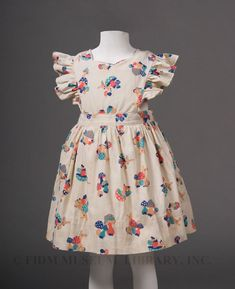 Girl's pinafore Printed cotton 1940-45 - A contemporary pinafore is a short-sleeved girl's dress, usually worn over a blouse or shirt and fastened up the back. When constructed from whimsical patterned textiles, a pinafore evokes carefree childhood