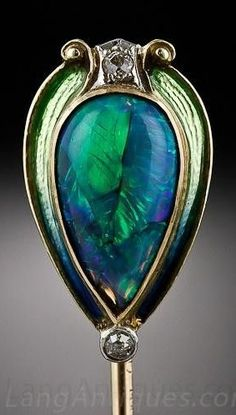 An Art Nouveau Opal Stick Pin. Centring a peacock-coloured, pear-shape black opal, weighing 1.50 carats, framed by a green enamel and diamond-set frame. #ArtNouveau #StickPin