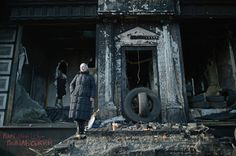 A woman poses for a photograph in front of a burnt out building near Independence square, where anti-government demonstrators continue to lay flowers and hold prayers for those killed in clashes with police last week on February 24, 2014 in Kiev, Ukraine. (Jeff J Mitchell/Getty Images) Ukraine's Revolution, One Year On