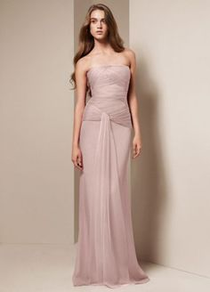 Long and luxurious bridesmaid dress with beautifully draped bodice and soft flowing sash.   Strapless column gown features asymmetrical draped bobbin net bodice and flowing sash.  Available in seleect stores and online.  Sizes 16-26 are available in stores only.  Fully lined.