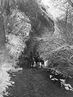 """Picture called """"Approaching Winter"""". The photograph presents Two Crow Indians on horseback in a shallow stream. They are flanked by beautiful snow-covered trees. They are riding beside a rock embankmnt. It was created in 1908 by Edward S. Curtis. (B&W copy)"""