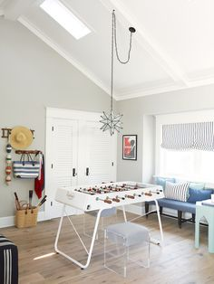 Burnham Design - Coastal game room features vaulted ceiling accented with skylight and Moravian Star Pendant illuminating a RS Barcelona Foosball Table and lucite stools situated across from louvered closet doors beside hooks. The back of the room boasts a small nook filled with window dressed in black and white striped roman shade over blue bench adorned with pillows.