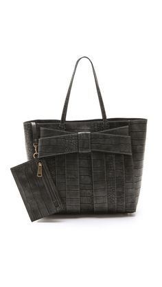 A croc-embossed ZAC Zac Posen tote is adorned with a signature bow and stripes. Double handles and metal feet. A magnetic tab opens the top to a faille-lined interior with 3 pockets and a detachable zip pouch. Dust bag included. @Shopbop
