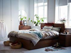 Une chambre claire de taille moyenne avec un lit brun associé à des tables de chevet et à une commode.