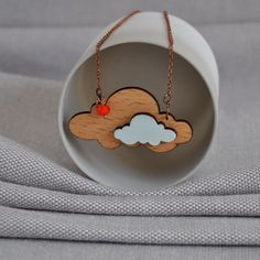This Cloud Origami style necklace from artysmartyshop.com is made from birch wood, carefully hand painted in pastel colors and finished with a durable varnish.  The chain is an vintage style antiqued copper with a lobster clasp, glass bead and 'artysmarty' rabbit tag.  There are also matching brooches in this series.