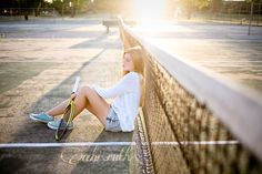 girls senior portraits with tennis racquet and tennis courts and pretty evening light