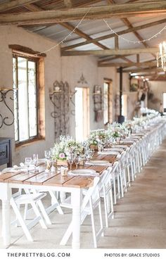 Long wooden tables with white chairs and rustic decor | Photograph by Grace Studios |