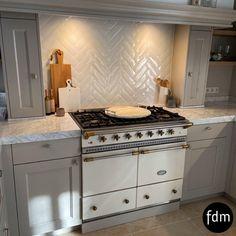 Deze prachtige klassiek, landelijke keuken in de kleur Elephant Breath van Farrow & Ball is prachtig afgewerkt met een wit Lacanche gasfornuis en een wit Carrara marmeren aanrechtblad.
