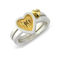 A lovingly handmade sterling silver and 22ct gold plated heart ring.Receive a complimentary pack of wildflowers with love seeds from the British Heart Foundation when you purchase a <em>Hearts of Gold</em> or <em>Little Golden Heart </em>ring. Available with silver frame and golden centre or golden frame nd silver centre. Also available with golden centre and an oxidised (black) surround for a more striking and dramatic look. Each ring is custom made to your size. Please indicate your ring…