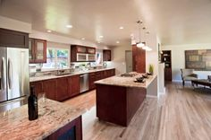, California Kitchen After Remodel Also Brown Modern Kitchen Cabinet And Kitchen Island Also Blonde Laminate Floor Also Cool Modern Pendant Lights And Stainless Refrigerator Also Elegant Living Room Furniture: Finding Some Good Kitchen Remodel Before And After Example For Good Kitchen Remodeling Ideas
