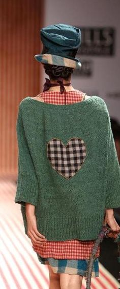 How cute. Green sweater plus black/ white check wool heart applique. Also, what a stupid, stupid hat.
