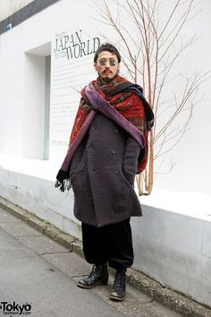 [The oversize scarf looks cool on him] Hummy's knitted coat is from The Viridi-anne and his baggy pants are Sonia Rykiel. He's wearing round sunglasses and an oversize scarf on top of his coat. He is also wearing earrings, piercings and lace-up boots.