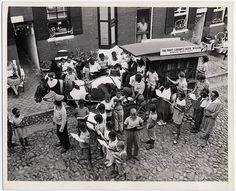 1945 Photograph of the Enoch Pratt Free Library book wagon during a visit to the 1000 block Dallas Street in Baltimore, Maryland. Gathered around this horse-drawn wagon and looking over the books before making a selection are numerous African American children and adults. In the background on this cobblestone street are brick houses with shuttered windows, hanging baskets, window boxes with flowers, and outdoor tables and chairs.