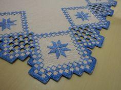 Centro de mesa bordado a mão, em ponto reto e hardanger  Tecido: etamine bege.  Linha: Esterlina nº5 na cor azul (nº 40).  Finalizado com uma mão de termolina leitosa nas beiradas.