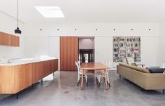 Modern home with Dining Room, Table, and Chair. The clients had an impressive collection of Scandinavian midcentury teak furniture that now pops beautifully against the concrete floors, white-painted brick, and pine v-joint walls. Photo of A Traditional 1920s Bungalow with a Boxy Modern Extension