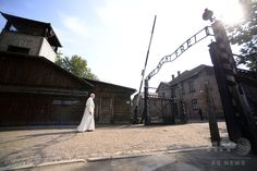 "Pope Francis walks towards the main entrance with the lettering ""Arbeit Macht Frei"" (Work Sets You Free) at the former Nazi German Auschwitz-Birkenau death camp on July 29, 2016 in Oswiecim as part of his visit to the World Youth Days (WYD). (c)AFP/FILIPPO MONTEFORTE"