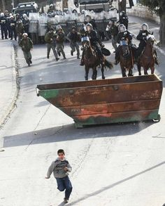 A boy runs from the Israeli police. We have been unable to confirm whether the boy is Palestinian. If anyone has more information about this photo, please let us know.