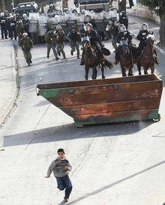A Palestinian boy runs from the Israeli Army