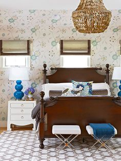 A+handsome,+richly+stained+bed+frame+with+a+classic+silhouette+is+the+dominate+figure+in+this+bedroom,+but+playful+patterns,+an+infusion+of+electric+blue,+and+glam+silhouettes+introduce+vitality+and+spark.+What+we+love:+Hybrid+style+that's+not+afraid+to+be+bold.+Modern+furniture,+such+as+the+X-base+ottomans+placed+at+the+foot+of+an+antique-inspired+bed,+demure+floral+wallpaper+as+a+background+for+funky+textiles,+and+soft+neutrals+teamed+with+zingy+indigo+all+make+for+unique+style+pairings.