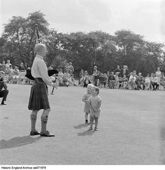AA071979 A man in a kilt playing the bagpipes at an open air event on Hampstead Heath watched by two small boys, spectators seated behind them. Hampstead Heath, Greater London Authority Date 1960 - 1965 Photographer: John Gay