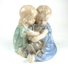 A Royal Copenhagen children with dog porcelain figurine by Christian Thomsen, circa 1924 - 1934. A Royal Copenhagen children with dog porcelain figurine by Christian Thomsen, circa 1924 - 1934. Modelled depicting two young children both closely embracing a dog, incised with a Christian Thomsen monogram to the lower back of the figure in blue, marked beneath with the green Royal Copenhagen Denmark stamp, three wavy lines in blue and numbered 707. 5.9 in (15 cm) height.