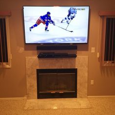 A 60in Tv Mounted Over The Fireplace With