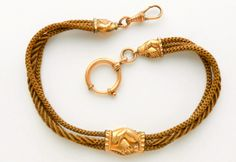 Victorian watch chain of human hair with gold clasped hand detail.