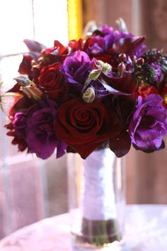 Fall bridal bouquet featuring deep purple lisianthus, deep red Heart roses, red hypericum berries, eggplant scabiosa, and deep red calla lilies