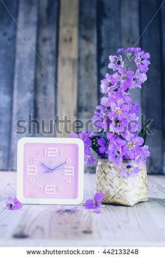 Bright pink wall clock on a wooden table. pastel tones. - stock photo