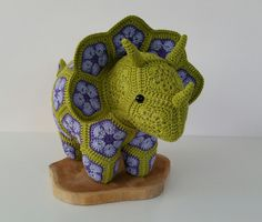 Crochet dinosaur Triceratops, handmade from african flowers. I used 100% cotton yarn in the colors green,purple and lavender. Crochet with hook 2,5. Size: approximately 53 cm width and 30 cm high. *Not suitable for younger children without supervision * Please take into consideration that the actual colour might be slightly different than your computer display. * All items are handmade with love in a smoke free environment and are ready to ship, unless stated otherwise. The dinosaur ...
